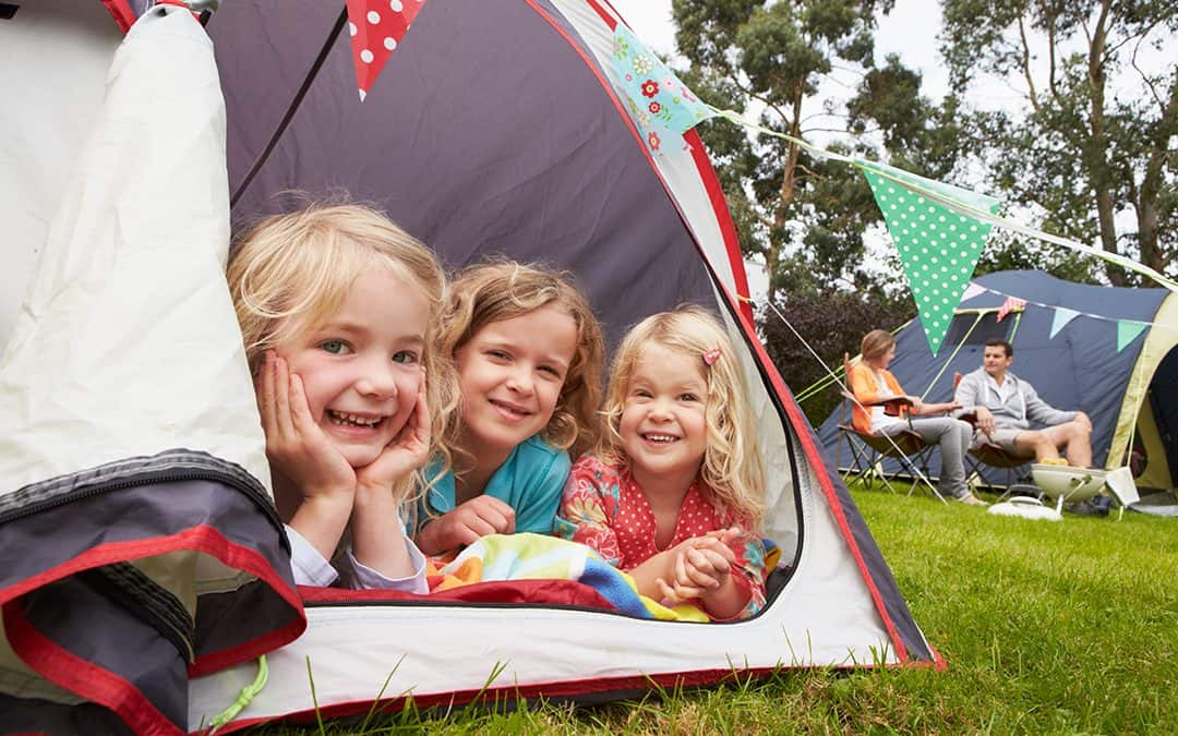 Kids in tent with pendant flag draping over during at-home staycation